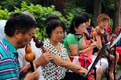 Det kinesiska folket som spelar på traditionella flöjter i Jingshan, parkerar royaltyfria foton