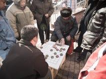 Det kinesiska folket spelar Xiangqi (kinesiskt schack) på gatasidan Arkivfoton
