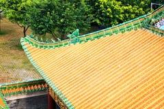 Det kinesiska taket av traditionell byggnad med klassisk guling glasade tegelplattor i Kina royaltyfri bild
