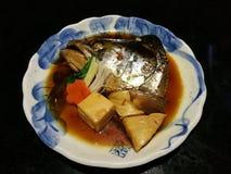 Det kokta laxhuvudet i söt soya tjänade som med moroten och tofuen i en lokal japansk restaurang, traditionell japansk mat, ström Arkivbilder