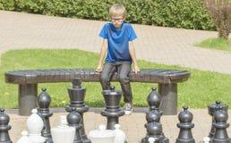 Det koncentrerade barnet och att tänka om hans nästa flyttning som sitter på en träbänk under en utomhus- schacklek som använder  royaltyfria foton
