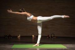 Det koncentrerade damanseendet i krigaren poserar, medan öva yoga royaltyfri foto
