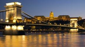 Det kungliga slottet och kedjar överbryggar på skymningen i Budapest Royaltyfria Bilder