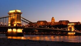 Det kungliga slottet och kedjar överbryggar på skymningen i Budapest Royaltyfria Foton
