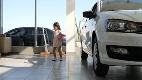 Det kvinnliga barnet roar i bilåterförsäljaren, bilförsäljningsmitten, den spelade flickan lager videofilmer