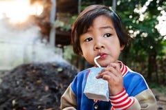 Det kvinnliga barnet som dricker exponeringsglas av, mjölkar Arkivfoto