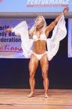 Det kvinnliga diagramet modell böjer henne muskler och visar henne fysik royaltyfria bilder