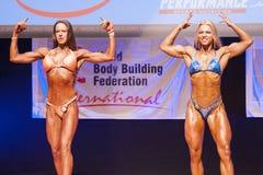 Det kvinnliga diagramet modell böjer henne muskler och visar henne fysik Royaltyfri Foto