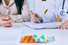 Det kvinnliga doktorsmötet med en patient i kontoret, ger hon ett recept till kvinnan Precis händer över tabellen Royaltyfri Foto
