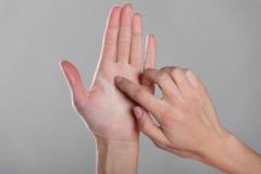 Det kvinnliga fingret trycker på en öppen hand Arkivfoton