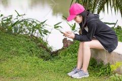 Det kvinnliga innehavet och ser den smarta telefonen i trädgård arkivfoto