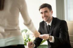 Det kvinnliga jobbsökandet ger meritförteckningen till rekryteraren på jobbintervjun Royaltyfri Bild