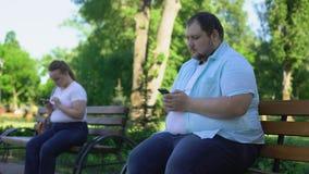 Det lätta feta folket meddelar i socialt nätverk men rädd bekant i verkligheten arkivfilmer