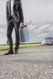 Det låga avsnittet av bärande bensin för den unga affärsmannen kan med den brutna bilen i bakgrund på bygd fotografering för bildbyråer