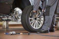 Det låga avsnittet av den manliga mekanikern som reparerar bilens gummihjul i reparation, shoppar royaltyfri fotografi
