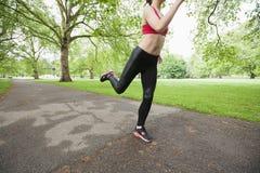 Det låga avsnittet av den unga kvinnan som in joggar, parkerar arkivbild
