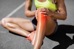Det låga avsnittet av idrottskvinnalidande från gemensamt smärtar fotografering för bildbyråer