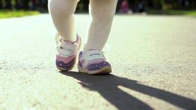 Det låga skottet av litet barnflickafot som kliver på bana i soligt, parkerar med föräldrar stock video