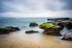 Det långa exporsurehavet och vaggar på stranden Fotografering för Bildbyråer