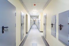 Det långa gula hallet med grå färger belägger med metall dörrar och golvet royaltyfria foton