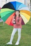 Det låtna leendet är ditt paraply Färgrik tillbehör för gladlynt lynne Långt hår för flickabarn som går med paraplyet stay arkivfoto