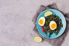 Det löskokta ägget och de stekte haricot vert kopiera avstånd äta för begrepp som är sunt Fotografering för Bildbyråer