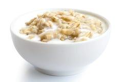 Det lagade mat hela havregrynet med mjölkar i den vita keramiska bunkeisolaen Royaltyfri Foto