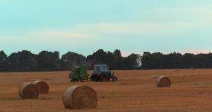 Det lantliga fältet i sommar med baler av hö, traktor släpper en höbal lager videofilmer