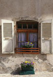 Det lantliga fönstret med gammalt trä stänger med fönsterluckor i det lantliga huset för stenen, Switz Arkivbild