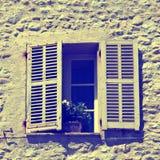 Det lantliga fönstret med gammalt trä stänger med fönsterluckor i lantligt hus för sten, bevisar Royaltyfri Fotografi
