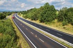 Det lantliga landskapet med en huvudväg fodrade med träd, den röda lastbilen och bilar på vägen Royaltyfria Bilder