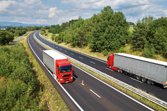 Det lantliga landskapet med träd fodrade huvudvägen, de röda lastbilarna för huvudvägritt två Arkivbild