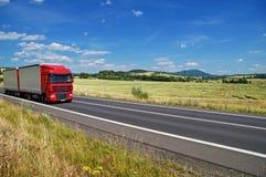 Det lantliga landskapet med vägen kör du en röd lastbil Royaltyfri Foto
