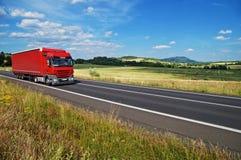 Det lantliga landskapet med vägen kör du en röd lastbil Royaltyfri Fotografi