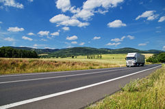 Det lantliga landskapet med vägen kör du en vit lastbil Arkivbild