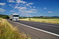 Det lantliga landskapet med vägen kör du en vit lastbil Royaltyfria Bilder