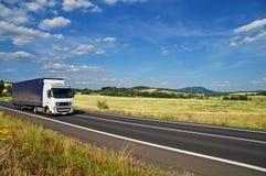 Det lantliga landskapet med vägen kör du en vit lastbil Arkivfoton