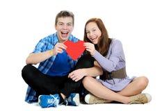 Det le tonårs- flicka- och pojkeinnehav en valentin klippte från rött skyler över brister ut royaltyfri foto