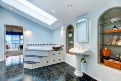 Det ledar- badrummet med blått marmorerar tegelplattagolvet, och hörnbadet badar Royaltyfri Bild