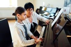 Det ledar- pianot visar studenten hur man rymmer hans hand arkivbild