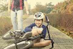 Det ledsna barnet får olycka med hans cykel royaltyfria bilder