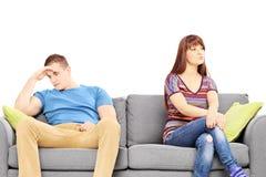 Det ledsna barnet kopplar ihop sammanträde på en soffa efter ett argument royaltyfri foto