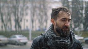 Det ledsna barnet uppsöker mannen i staden under häftig snöstorm arkivfilmer