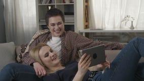 Det lesbiska paret vilar på soffan, använder minnestavlan och skrattar, den unga familjen, plädet, slags tvåsittssoffa 60 fps stock video