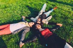 Det liggande huvudet för lyckliga tonåringar - - head på deras baksidor på det gröna gräset Arkivbild