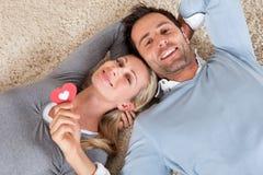 Det liggande huvudet för mannen och för kvinnan - - head på mattan Arkivfoton