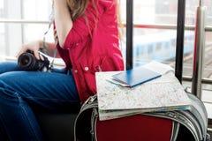 Det ligger på ett resväska- och passkort på bakgrundsflicka i ett rött omslag, som inte är in fokusen Arkivbild