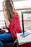 Det ligger på ett resväska- och passkort på bakgrundsflicka i ett rött omslag, som inte är in fokusen Royaltyfri Fotografi