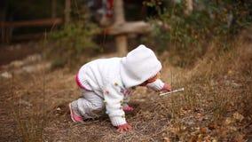 Det lilla barnet försöker att stå upp från jordningen och att ta upp en plast- pinne lager videofilmer