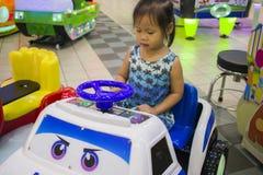 Det lilla barnet kör barnleksakbilen i nöjesfältsommardag royaltyfri foto